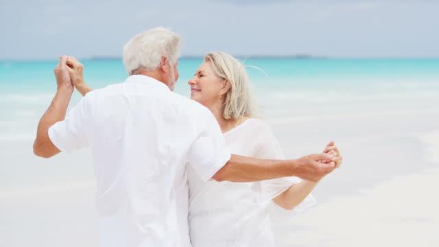 Senior Caucasian couple sharing kiss on tropical beach