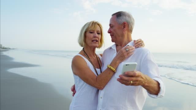 Senior Caucasian couple taking selfie on beach vacation video