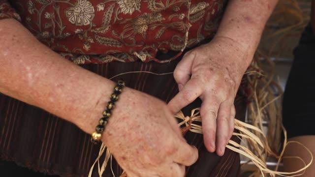 senior kaukasiska kvinnliga vävning korg på hantverk verkstad. närbild video av kvinnans händer att göra hantverk - halmslöjd bildbanksvideor och videomaterial från bakom kulisserna