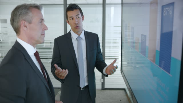 Senior Caucasian man and Asian male colleague discussing the numbers shown in the financial presentation on the large screen in the meeting room
