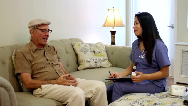 senior caucasian man at home talks with asian caregiver - senior care stock videos and b-roll footage