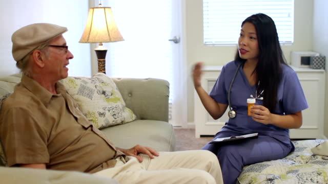 Senior Caucasian Man at Home Talks with Asian Nurse video