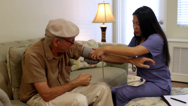 Senior Caucasian Man Blood Pressure Checked by Asian Nurse video