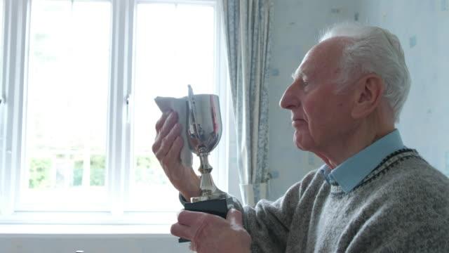 Senior Caucasian man cleaning his trophy
