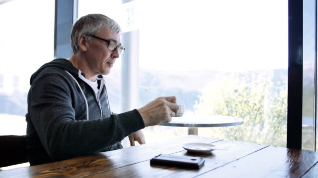 Senior caucasian sport style man looking out the window at the cafe. Aged gray man enjoying drinking coffee at the table with cellphone video