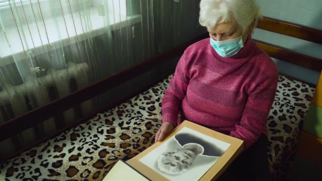 Senior kaukasiska kvinna i skyddande mask i ansiktet tittar på hennes porträtt på foto i hennes rum hemma video