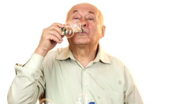 Senior cheerful man blowing bubbles isolated on white video