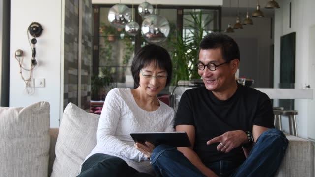 stockvideo's en b-roll-footage met senior chinees paar kijken tablet thuis - een tablet gebruiken
