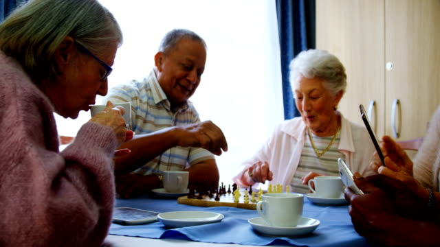 Senior citizens using mobile phone and digital tablet while playing chess 4k video