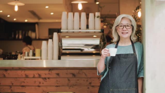 vídeos de stock e filmes b-roll de senior coffee shop owner standing in front of her cafe - avental