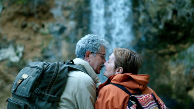 Senior couple admiring beautiful waterfall Senior couple is kissing and enjoying the view on beautiful waterfall in spring day. kissing stock videos & royalty-free footage