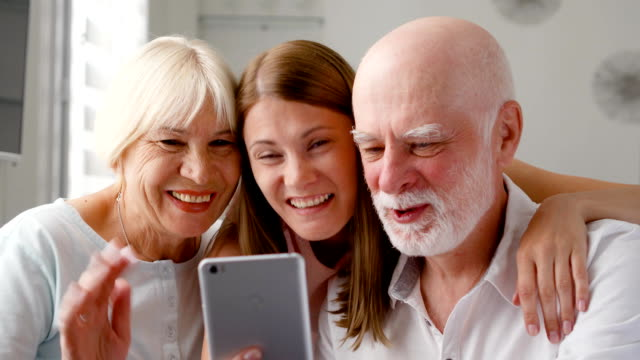 Senior couple and their daughter at home talking via messenger Skype on mobile. Smiling laughing video