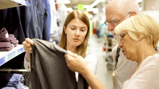 Senior couple and their daughter shopping in mall. Standing near shelves with clothes video