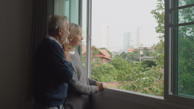 vídeos de stock e filmes b-roll de 4k, senior couple are peering out the window. - old men window