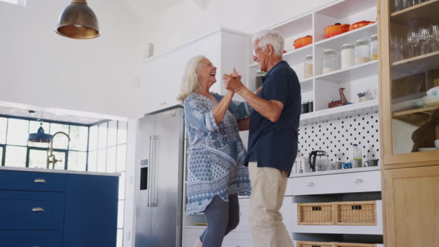senior couple at home dancing in kitchen together - coppia anziana video stock e b–roll
