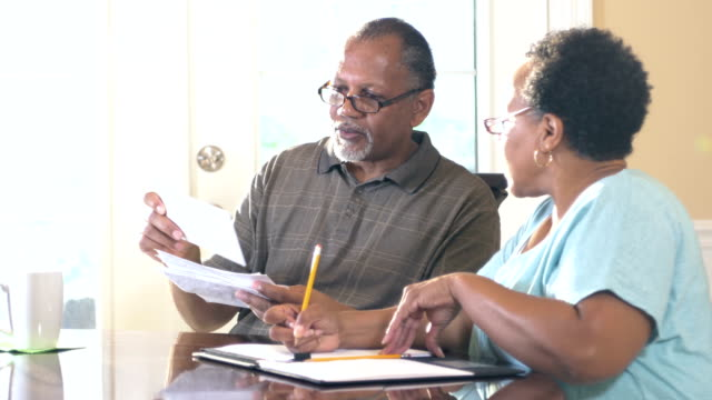 Senior couple at home paying bills A senior African-American couple at home looking through a stack of bills to be paid. The woman is writing notes as they discuss their home finances. financial bill stock videos & royalty-free footage