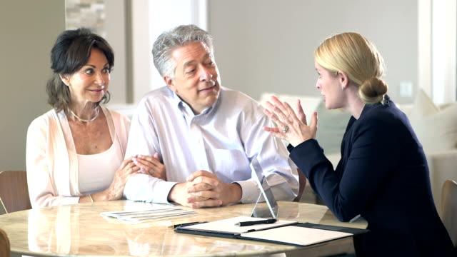 vídeos de stock e filmes b-roll de senior couple at home talking to financial planner - senior business woman tablet
