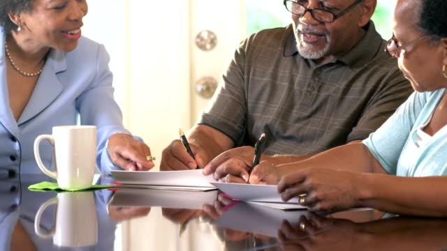 vidéos et rushes de couples aînés à la maison avec le conseiller financier - vendre