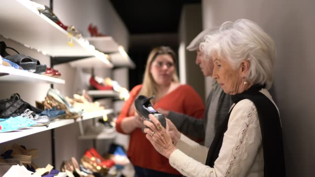 Senior couple being helped by a saleswoman while shopping for shoes in a thrift store