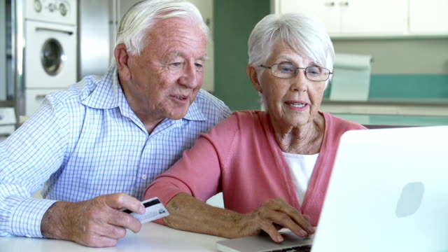Senior Couple Booking Vacation Online Using Digital Tablet video