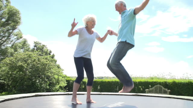 Senior Couple Bouncing On Trampoline In Slow Motion video