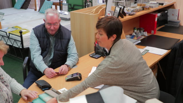 Senior Couple Buying a New Bed Senior couple are buying a new bed and are paying at a desk with a sales clerk. They are deciding on the design with color swatches. saleswoman stock videos & royalty-free footage