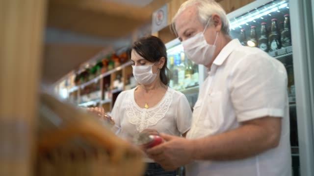 senior-paar kaufen mit gesichtsmaske im geschäft - krankheitsverhinderung stock-videos und b-roll-filmmaterial