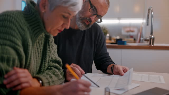 Senior couple checking bills expenses together at home