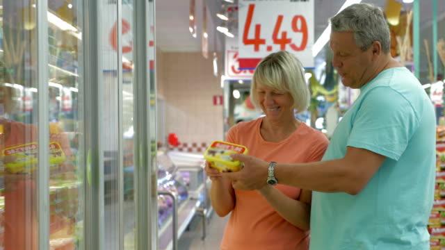 пожилая пара, выбирая продукты в магазин - замороженные продукты стоковые видео и кадры b-roll
