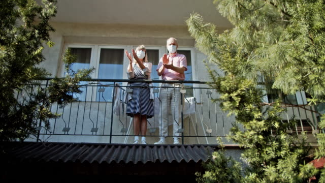 senior couple clapping from balcony during covid-19 quarantine - battere le mani esprimere a gesti video stock e b–roll
