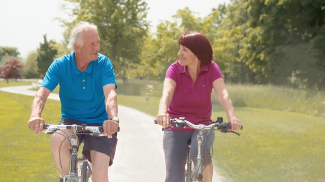SLO MO Senior couple cycling through the park video