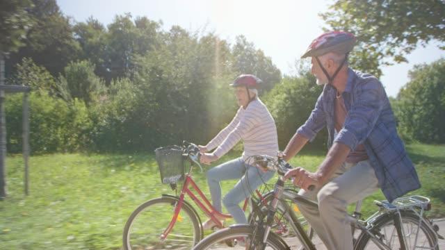 älteres paar ts radfahren durch den sonnigen park - aktiver senior stock-videos und b-roll-filmmaterial