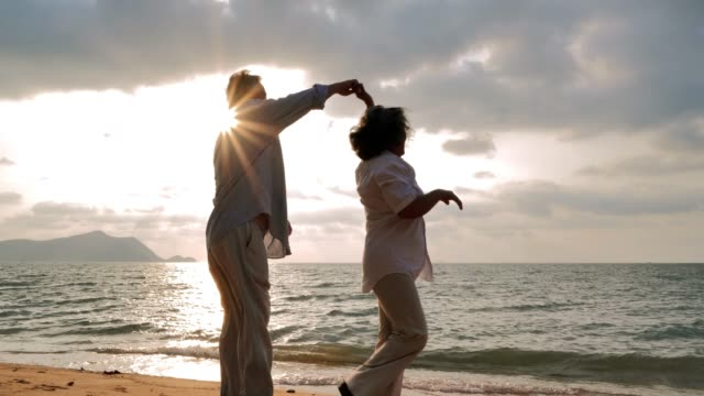Senior couple dancing at beach on sunny day ,Senior couple relaxing by the sea.Senior Holidays,Vacations