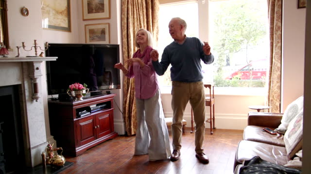 Senior Couple Dancing At Home Slowmo shot of senior couple dancing together in the living room of their home. love emotion stock videos & royalty-free footage