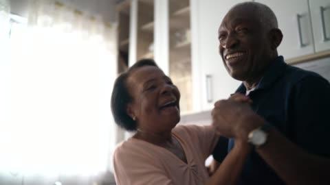 vídeos de stock e filmes b-roll de senior couple dancing at kitchen - felicidade