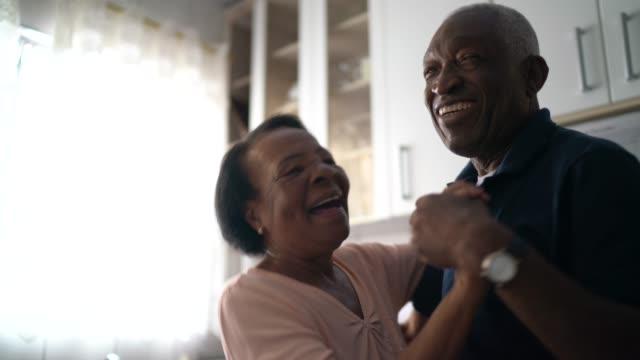 senior paar tanzen in der küche - aktiver senior stock-videos und b-roll-filmmaterial