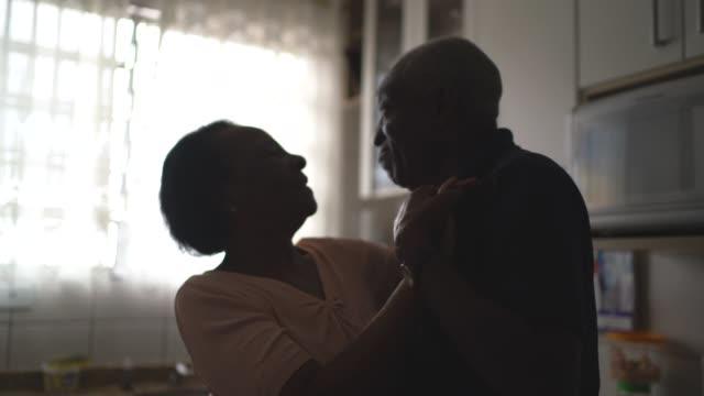 coppia senior che balla in cucina - love video stock e b–roll