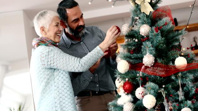 Senior couple decorating a Christmas tree 4k video