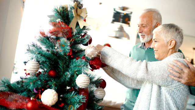 Senior couple decorating a Christmas tree. video