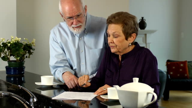 senior couple discuss documents - bills and taxes stock videos & royalty-free footage