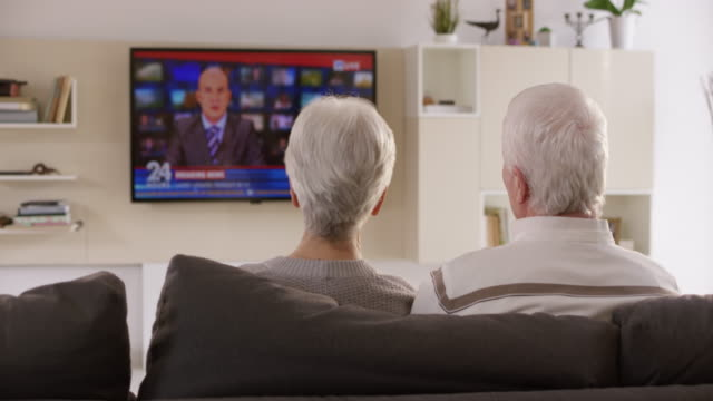 DS Senior couple discussing news they are watching on TV Wide rear view dolly shot of a senior couple sitting on the sofa and watching the news on TV. They are having a discussion about it. Shot in Slovenia. watching tv stock videos & royalty-free footage