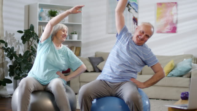 Senior Couple Doing Side Bend Exercise on Stability Balls