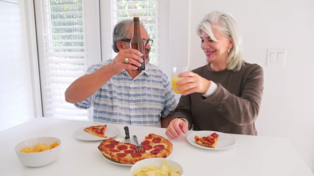 Senior couple eating pizza and toasting at home