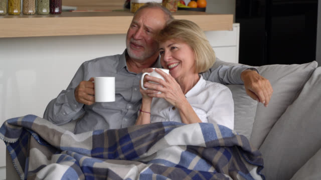 Senior couple enjoying a coffee cuddling together on couch while watching TV talking and smiling Senior couple enjoying a coffee cuddling together on couch while watching TV talking and smiling – Lifestyles blanket stock videos & royalty-free footage