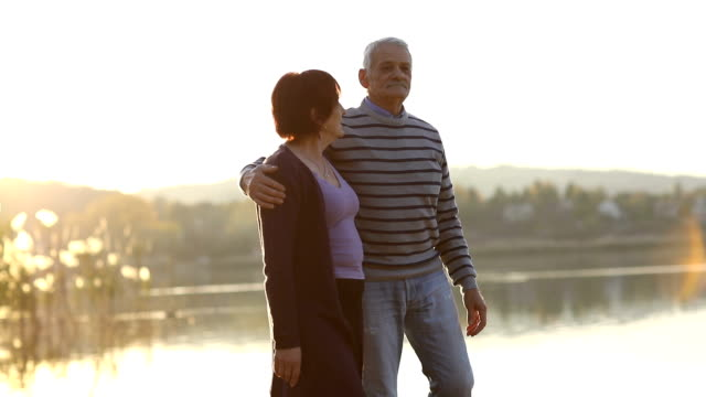 Senior couple enjoying autumn day by the lake video