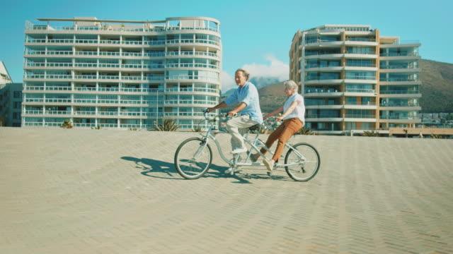 Senior couple enjoying on tandem bike in summer