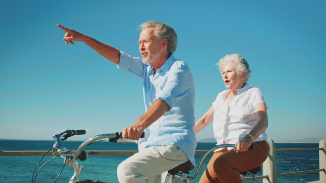 senior couple enjoying tandem bicycle on sunny day - retirement stock videos and b-roll footage