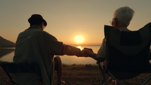 äldre par njuter solnedgången vid sjön, slow motion - pensionärsmän bildbanksvideor och videomaterial från bakom kulisserna