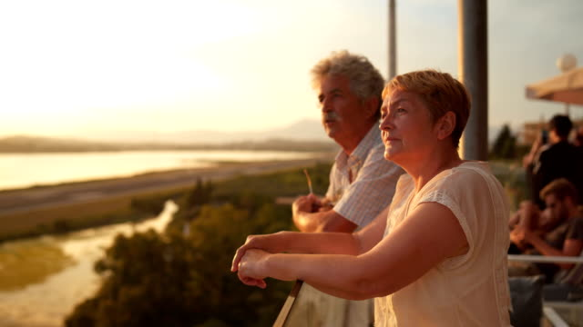senior couple enjoying the view of the sunset - 60 64 года стоковые видео и кадры b-roll