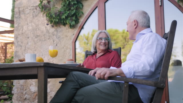 Senior Couple Face to Face and Smiling at Outdoor Breakfast video